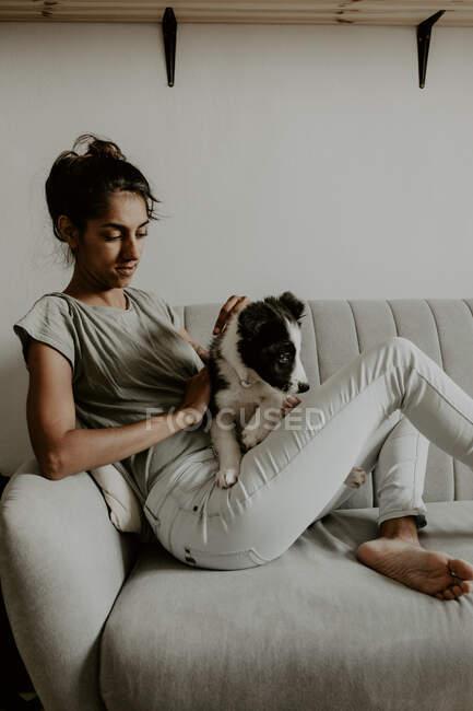 Підліток з милим цуценям на дивані. — стокове фото