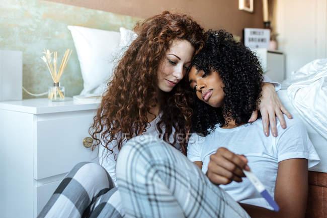 Молодая женщина утешает другую женщину, недовольную тестом на беременность — стоковое фото