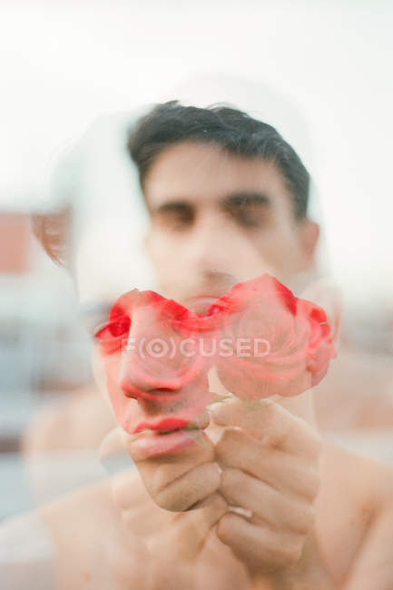 Brunette young shirtless guy showing vinous fresh roses and looking at camera on blurred background — Stock Photo