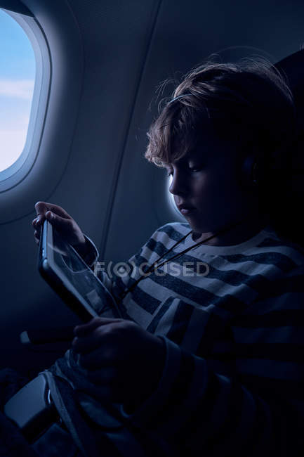 Cute boy watching film on tablet in plane — Stock Photo