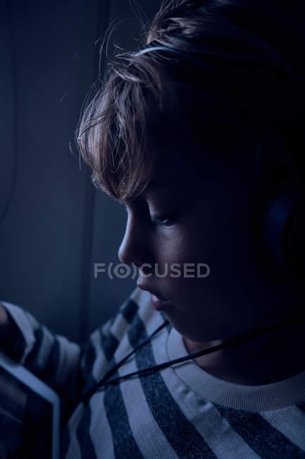 Lindo chico viendo la película en la tableta en avión - foto de stock