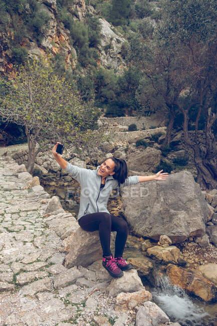 Jolie femme en tenue décontractée souriant joyeusement et utilisant un smartphone moderne pour prendre des selfies tout en étant assis sur la roche près du ruisseau avec de l'eau douce propre dans un parc majestueux — Photo de stock