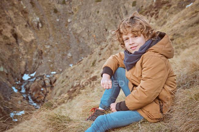 Mignon garçon assis sur la colline près du ruisseau — Photo de stock