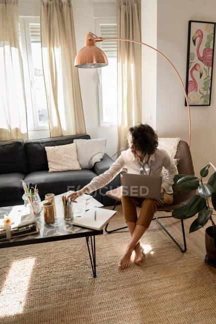Жінка з ноутбуком сидить на стільці біля низького столу з пензлями та олівцями в банках і простирадлах у світлій кімнаті. — стокове фото