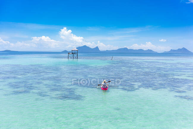 Back view male boating on canoe with paddle on amazing azure sea and blue sky in Malaysia — Stock Photo