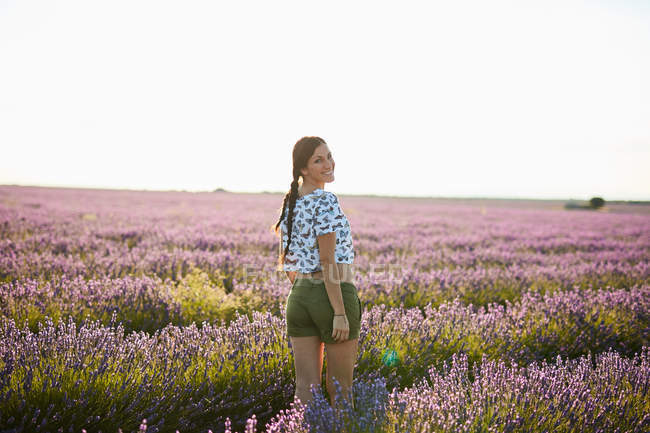 Young woman walking between violet lavender field — Stock Photo