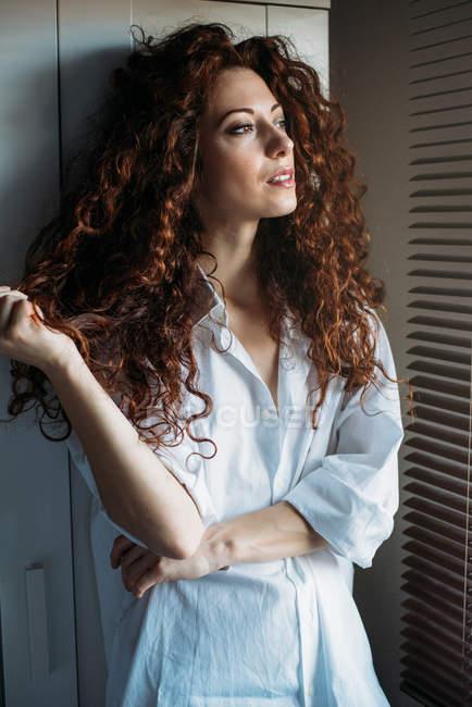 Bella donna premurosa in piedi vicino a una finestra cieca — Foto stock