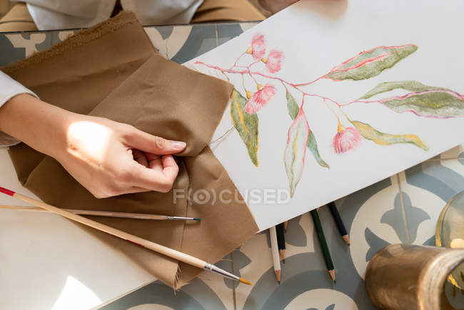 Cropped image of woman with material at table with paint on sheet, pencils and brushes — Stock Photo