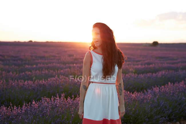Jovem mulher de pé em retroiluminação entre o campo de lavanda violeta — Fotografia de Stock