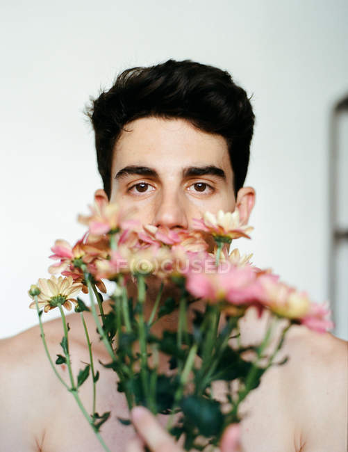 Brunette young shirtless guy holding rose fresh flowers looking at camera on grey background — стокове фото