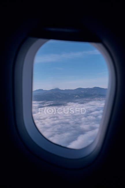 Vue des nuages blancs et la crête de la montagne de la fenêtre de l'aviation moderne — Photo de stock