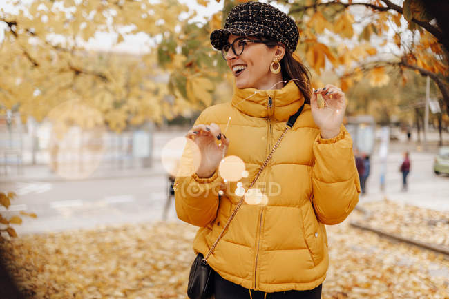 Cheerful young woman in stylish warm clothes standing near tree on autumn street — Stock Photo