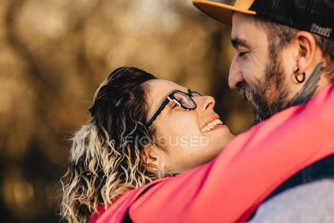 Счастливая пара смотрит друг на друга в солнечную погоду — стоковое фото