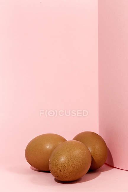 Œufs de poulet bruns crus sur fond rose — Photo de stock