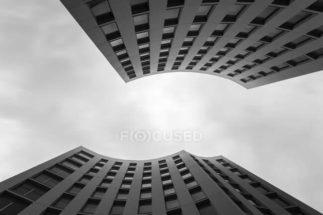 Desde abajo plano de magnífico edificio moderno de forma inusual contra cielo nublado - foto de stock