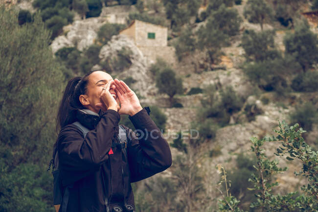 Beautiful woman with backpack holding hands near mouth and screaming loudly while standing in magnificent nature in Soller, Spain — Stock Photo
