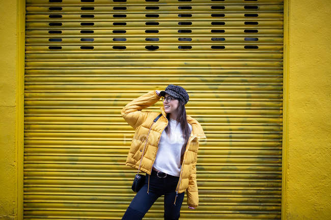 Smiling young woman in stylish outfit looking away while standing in front of yellow building wall on street — Stock Photo