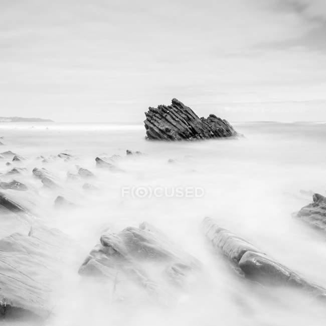 Бушующее море, катящееся у берега в облачный день — стоковое фото
