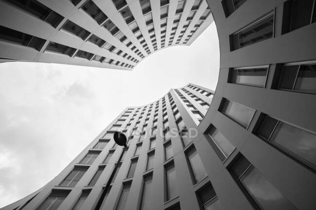 From below shot of magnificent modern building of unusual shape against overcast sky — Stock Photo