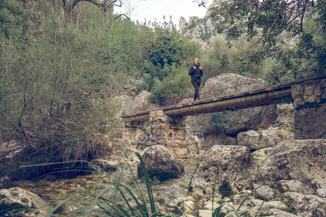 Woman with backpack standing on small bridge near a river in wonderful park in Soller, Spain — Stock Photo
