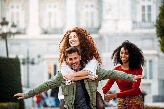 Three young friends playing piggy back in the streets of Madrid on winter — Stock Photo