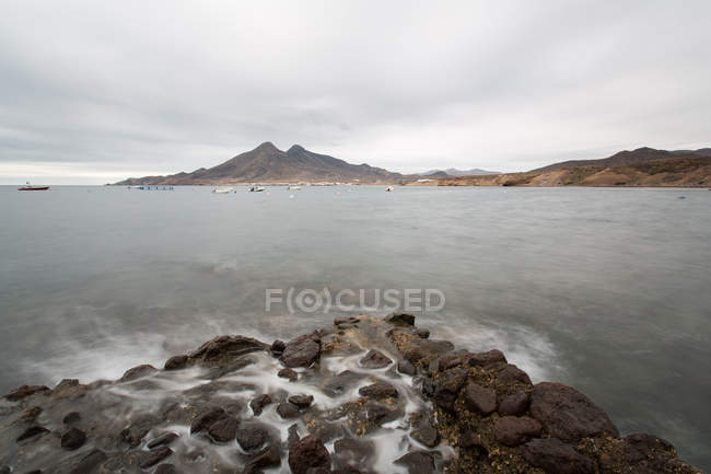 Mar tempestuoso e costa rochosa sob céu nublado — Fotografia de Stock