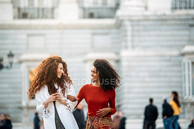 Duas jovens mulheres alegres andando nas ruas de Madrid no inverno — Fotografia de Stock