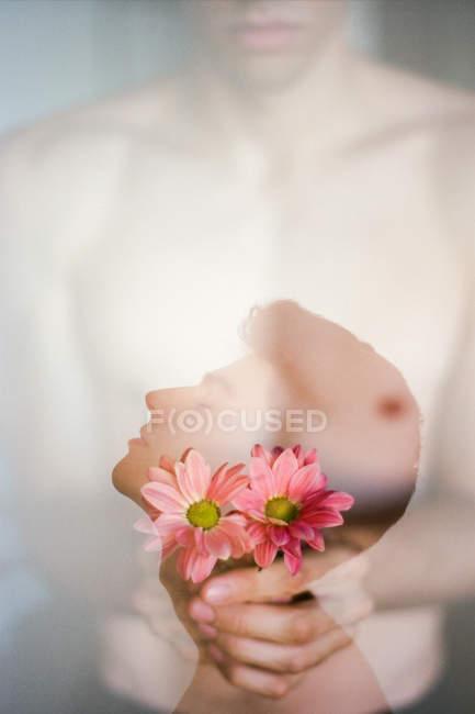 Doppelbelichtung eines brünetten jungen Mannes und ein Strauß frischer Blumen auf verschwommenem Hintergrund — Stockfoto