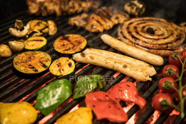 Closeup slices of assorted vegetables and meat frying on hot grill — Stock Photo