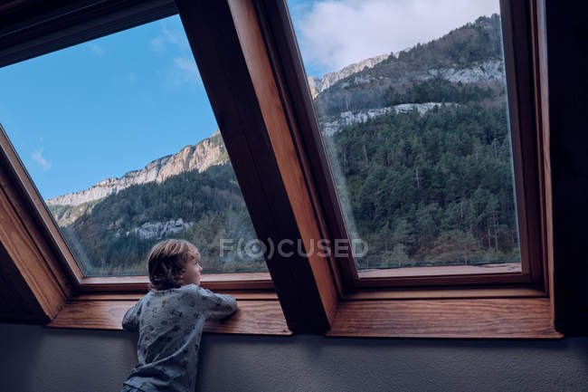 Boy looking at mountain through window — Stock Photo