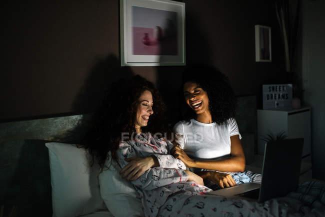 Молодые веселые друзья в постели развлекались за компьютером, смотря фильмы по ночам — стоковое фото