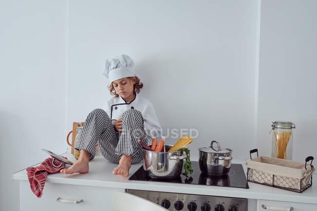 Задумчивый Маленький повар сидит возле кастрюли с овощами на электрической плите в современной светлой кухне — стоковое фото
