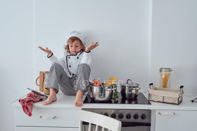 Смущенный Маленький повар, сидящий возле кастрюли с овощами на электрической плите в современной светлой кухне — стоковое фото