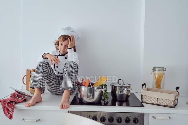 Смішні маленький кухар сидить поруч каструлі з овочами на електроплиті в сучасній кухні світла — стокове фото