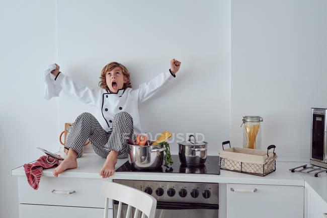 Грайливий маленький кухар сидить поруч каструлі з овочами на електроплиті в сучасній кухні світла — стокове фото