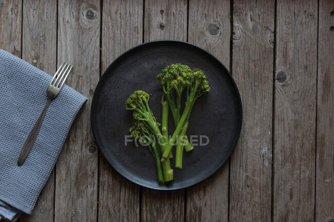 From above shot of fork and napkin lying near plate with healthy green broccoli — Stock Photo