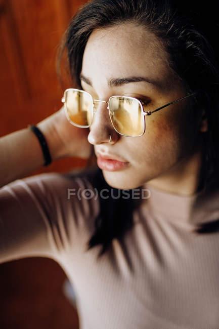 Portrait d'une jeune femme avec des lunettes jaunes — Photo de stock