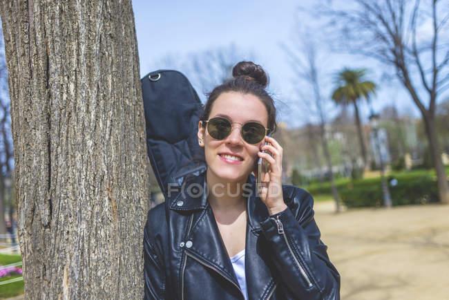 Vista lateral de uma jovem hipster rindo de pé e inclinada em uma árvore no parque no dia ensolarado, usando um telefone móvel — Fotografia de Stock