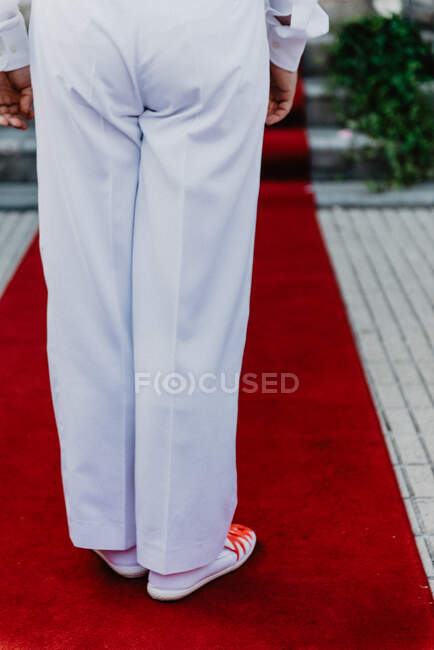 Людина в білій сукні і спортивному взутті стрибає на червоній доріжці — стокове фото