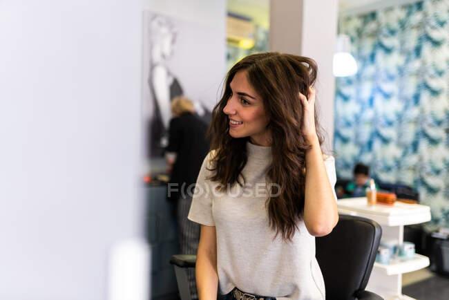 Згадка про молоду вродливу жінку, що торкається волосся і дивиться на дзеркало в перукарні салону. — стокове фото