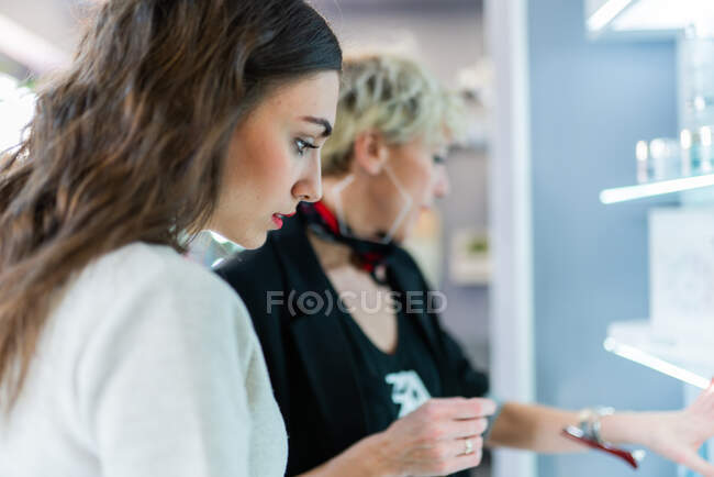 Aged hairstylist showing something to attractive slim woman in hairdressing salon — Stock Photo