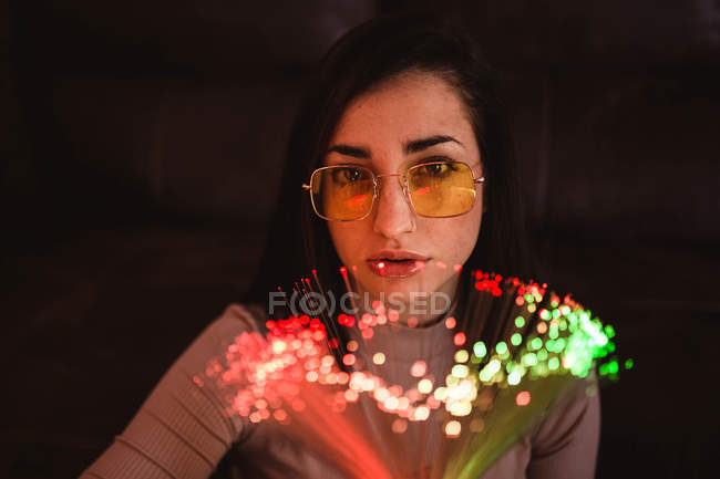 Young woman with fairy lights in darkness — стокове фото
