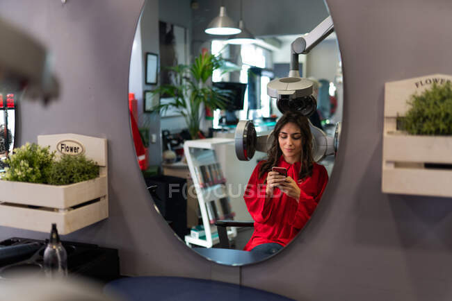 Side view of cheerful lady holding mobile phone and drying hairs in hairdressing salon — Stock Photo