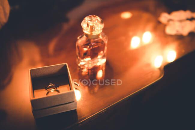 Anillo de oro de arriba en caja actual cerca de botella de aroma en mesa de madera - foto de stock