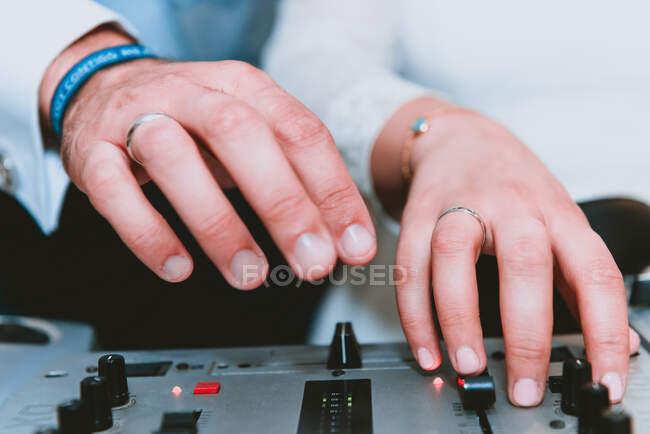 Crop man using music equalizer — Stock Photo