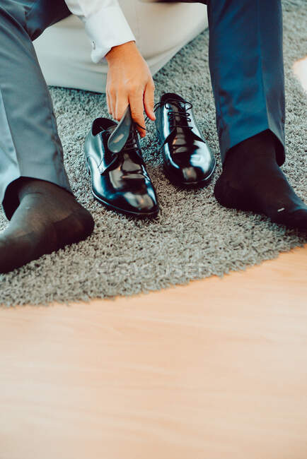 Crop male in trousers sitting and wearing black elegant boots on carpet — Stock Photo