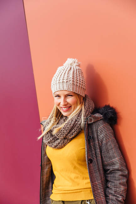 Chica rubia apoyada en una pared colorida - foto de stock