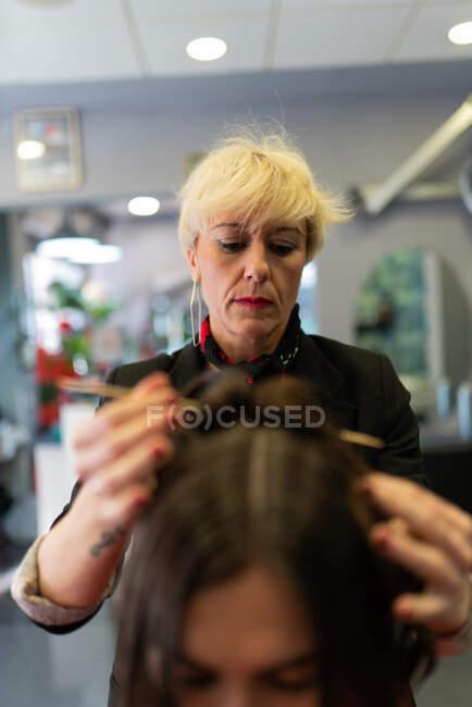 Stilista anziano rendendo acconciatura attraente giovane signora nel salone di parrucchiere — Foto stock