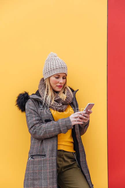 Retrato de menina loira escrevendo em seu telefone encostado a uma parede colorida — Fotografia de Stock