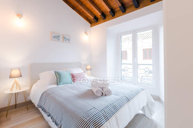 Comfortable light room with big bed and lamps near window in modern house — Stock Photo